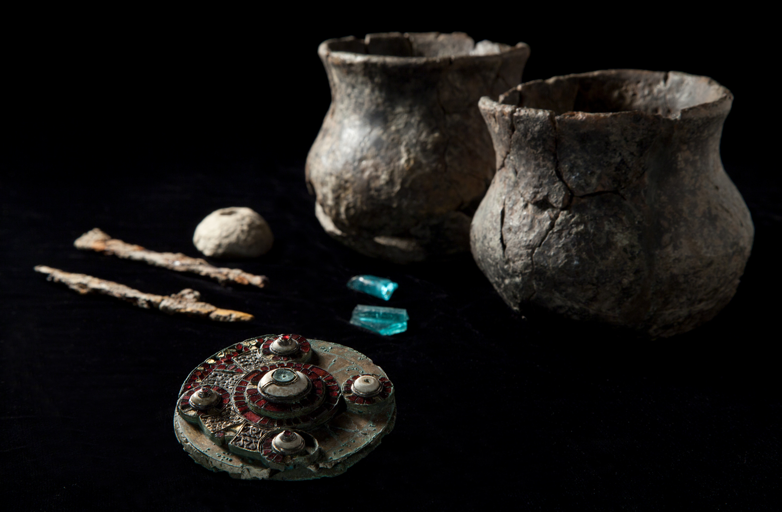 A photo of the burial assemblage discovered at West Hanney, including two fragments of glass (apparently from the same vessel), a chalk and spindle whorl, iron knives,and, two small ceramic vessels (most likely cups).